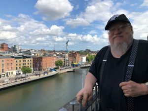 George RR Martin standing near river in Dublin